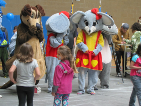 Two students interacting with two people in mouse and dog costumes
