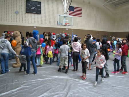 Students interacting with people in animal costumes in a gym