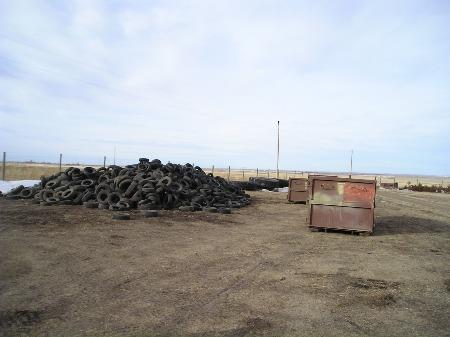 Large pile of used tires next to dumpster
